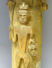 carved figure of a warrior carrying a head